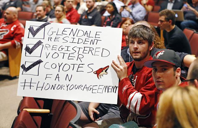 In this photo taken Wednesday, June 10, 2015, Arizona Coyotes fans Chris Webb, second from right, and Andrew Hill show their support for their team as the as the Glendale Council votes to back out of an arena lease agreement with the NHL team during a special council meeting in Glendale, Ariz. (David Kadlubowski/The Arizona Republic via AP) MARICOPA COUNTY OUT; MAGS OUT; NO SALES; MANDATORY CREDIT
