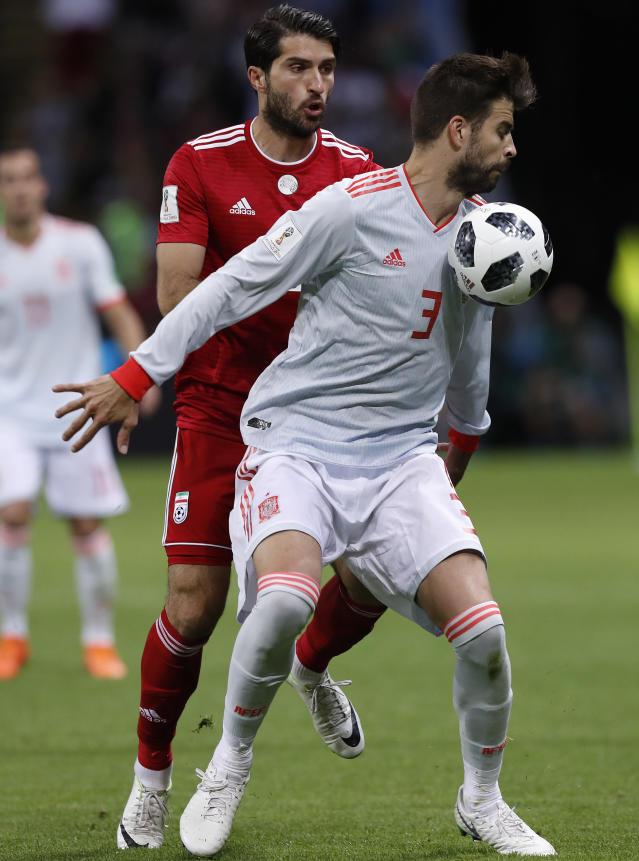 Spain's Gerard Pique, front, shields the ball, as Iran's Karim Ansarifard challenges him, during the group B match between Iran and Spain at the 2018 soccer World Cup in the Kazan Arena in Kazan, Russia, Wednesday, June 20, 2018. (AP Photo/Manu Fernandez)