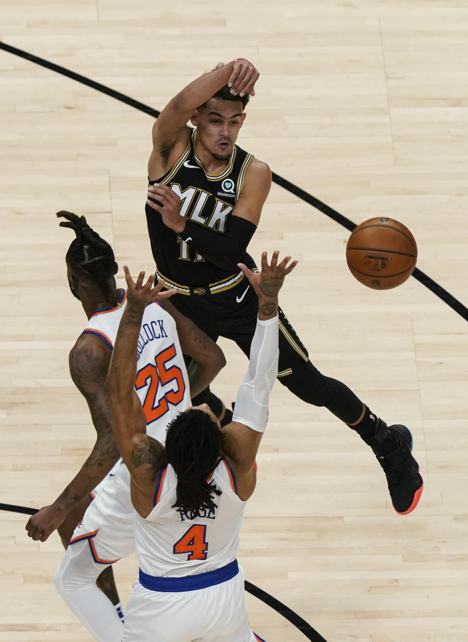 Atlanta Hawks' Trae Young (11) passes the ball against New York Knicks' Derrick Rose (4) and Reggie Bullock (25) during the first half in Game 4 of an NBA basketball first-round playoff series Sunday, May 30, 2021, in Atlanta. (AP Photo/Brynn Anderson)