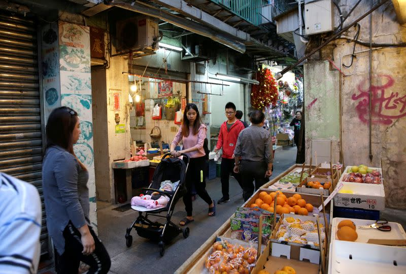 People walk past roadside stalls in an alley in Macau