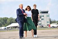 Melania Trump boards Air Force One in New Jersey with Donald Trump and Barron Trump wearing a loose white tee tucked into a green Fendi midi skirt and a pair of floral Christian Louboutin pumps. [Photo: Getty]