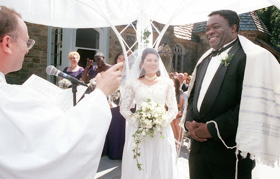 Rabbi Joel Braude, left, makes a toast during the wedding ceremony for actor Yaphet Kotto, right, and his bride Tessie Sinahon in Baltimore, Md., Sunday, July, 12, 1998. Kotto plays the imposing Lt. Al Giardello pn NBC's police drama
