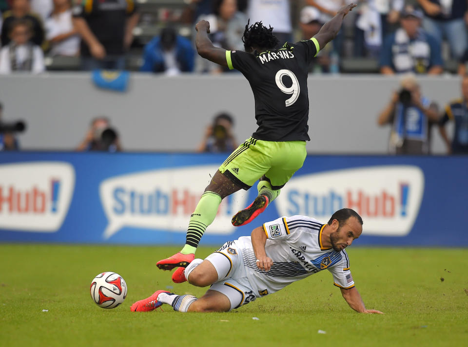 CORRECTS NAME OF GALAXY FORWARD TO LANDON DONOVAN - Los Angeles Galaxy forward Landon Donovan, right, goes after the ball as Seattle Sounders FC forward Obafemi Martins jumps over him during the first half of a Major League Soccer playoff game, Sunday, Nov. 23, 2014, in Carson, Calif. (AP Photo/Mark J. Terrill)