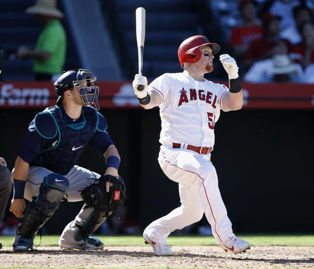 Los Angeles Angels' Kole Calhoun, right, hits a solo home run with Seattle Mariners catcher Mike Zunino watching during the seventh inning of a baseball game in Anaheim, Calif., Sunday, Sept. 16, 2018. (AP Photo/Alex Gallardo)