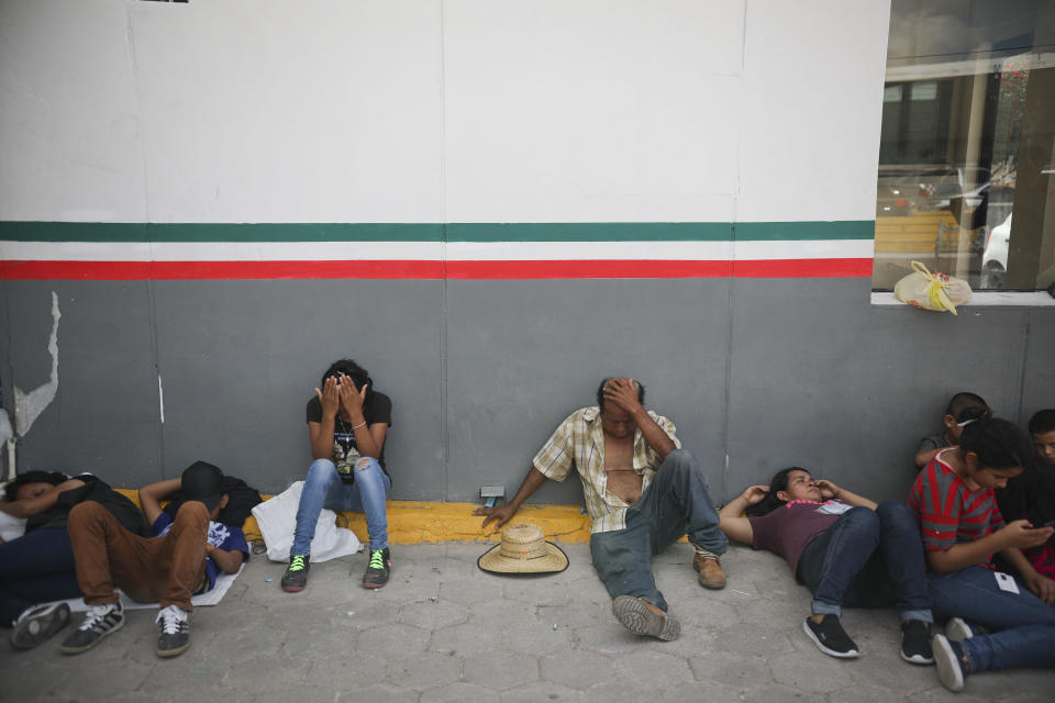 FILE - In this Aug. 1, 2019, file photo, migrants rest near a Mexican immigration center where people have set up a camp to sleep in Matamoros, Mexico, on the border with Brownsville, Texas. A published report says former Homeland Security Secretary Kirstjen Nielsen ordered officers to stop people from stepping on U.S. soil at official crossings with Mexico to claim asylum when she was U.S. Homeland Security secretary, undercutting her public statements at the time that they were welcome to do so. (AP Photo/Emilio Espejel, File)
