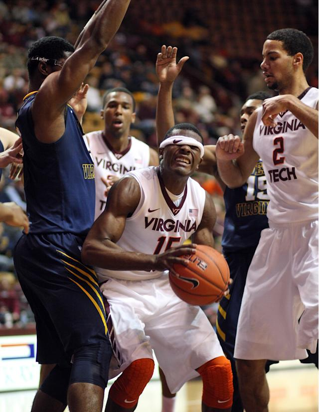 Virginia Tech guard Ben Emelogu (15) struggles with his headband under the basket during the first half of an NCAA college basketball game against West Virginia, in Blacksburg, Va., Tuesday, Nov. 12, 2013. (AP Photo/The Roanoke Times, Daniel Lin)
