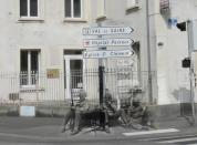 """Soldiers rest against the signs to a church and a hospital. Older versions of the signs are visible below them.<br><br>(<a href=""""http://www.flickr.com/photos/hab3045/collections/72157629378669812/"""" rel=""""nofollow noopener"""" target=""""_blank"""" data-ylk=""""slk:Courtesy of Jo Teeuwisse"""" class=""""link rapid-noclick-resp"""">Courtesy of Jo Teeuwisse</a>)"""