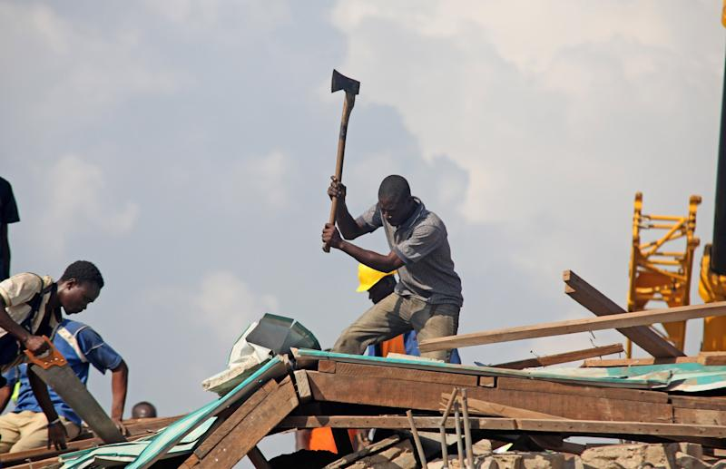Rescue workers clear rubble from the remainder of a collapsed building in Accra, Ghana, Wednesday, Nov. 7, 2012. A five-story shopping center built earlier this year in a bustling suburb of Ghana's capital collapsed Wednesday, killing at least one person and leaving several dozen people trapped in the rubble, authorities and eyewitnesses said. (AP Photo/ Christian Thompson)
