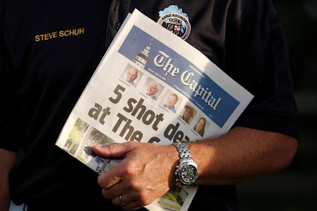 <p>Steve Schuh, the County Executive of Anne Arundel County, Maryland, holds a copy of the Capital Gazette as he is interviewed the day after a gunman killed five people and injured several others at the newspaper's offices, in Annapolis, Md., June 29, 2018. (Photo: Joshua Roberts/Reuters) </p>