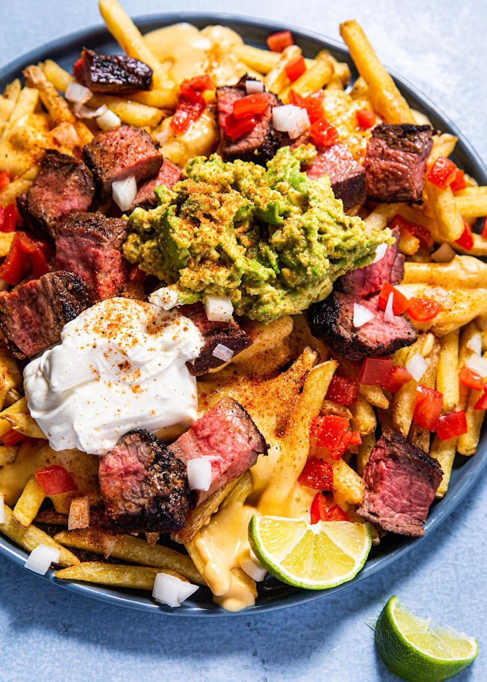 """<p>What a picture perfect plate of fries topped with a heaping amount of steak, guac, sour cream, lime, and more!</p><p>Get the recipe from <a href=""""https://www.delish.com/cooking/recipe-ideas/a30502519/carne-asada-fries-recipe/"""" rel=""""nofollow noopener"""" target=""""_blank"""" data-ylk=""""slk:Delish"""" class=""""link rapid-noclick-resp"""">Delish</a>.</p>"""