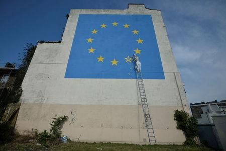 New Brexit-themed Banksy shows workman chipping away at European Union  flag