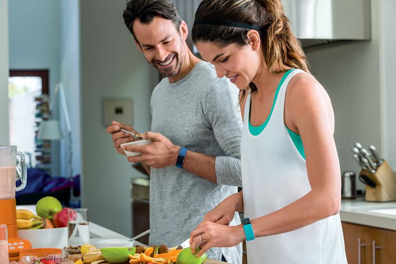 A couple wearing Fitbit Charge 2 trackers while cutting up fruit in a kitchen.