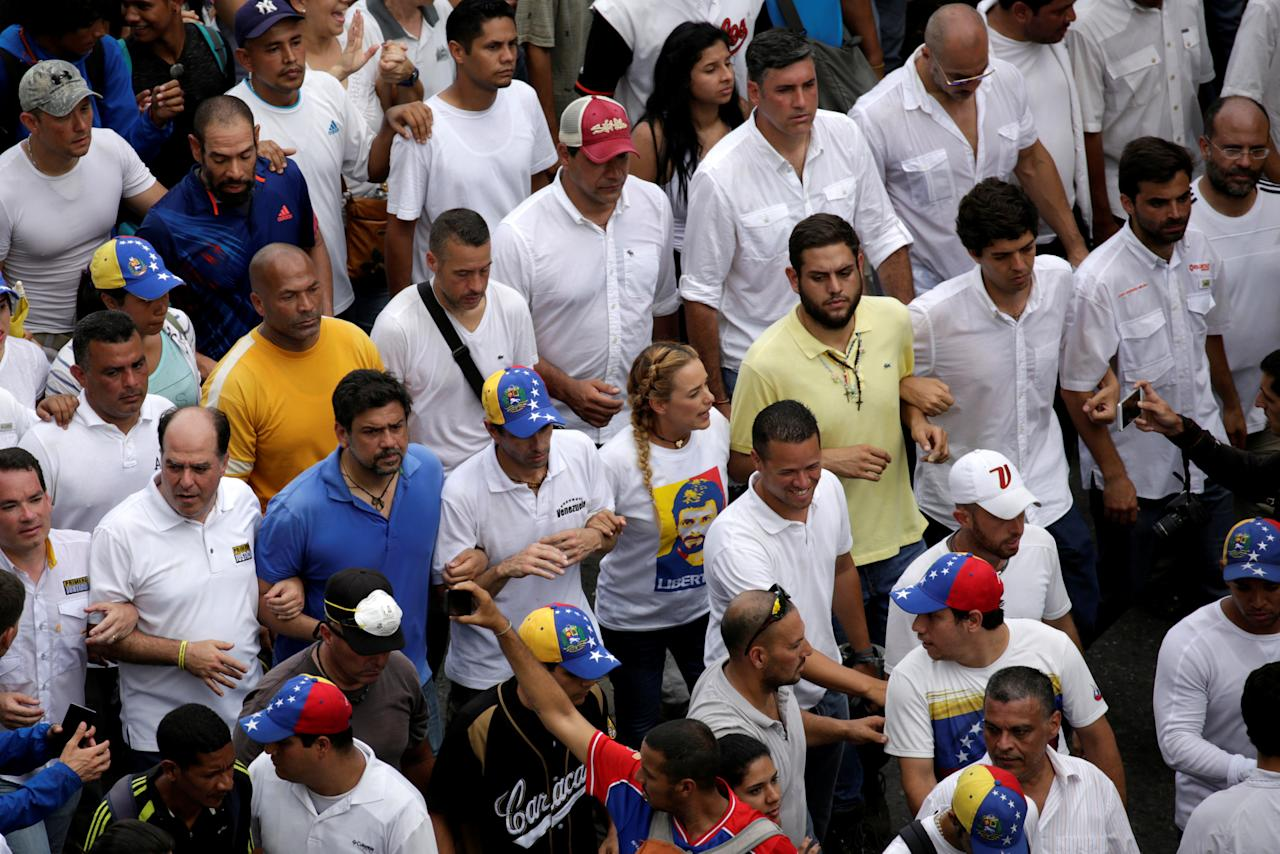 Venezuelan opposition leader and Governor of Miranda state Henrique Capriles and Lilian Tintori, wife of jailed opposition leader Leopoldo Lopez, walk with lawmakers and opposition leaders as they take part in a rally to honour victims of violence during a protest against Venezuela's President Nicolas Maduro's government in Caracas, Venezuela, April 22, 2017. REUTERS/Marco Bello