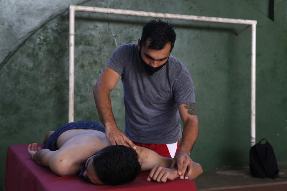 Midfielder Fulvio Duarte of the Fulgencio Yegros football club, massages a volunteer in a gym at San Roque Gonzalez University, in San Lorenzo, Paraguay, Friday, Feb. 5, 2021. The 31-year-old soccer player who has played for 13 years, is now finishing his studies as a physiotherapist while he works with his wife in an online shop of orthopedic products to survive during the COVID-19 pandemic. (AP Photo/Jorge Saenz)