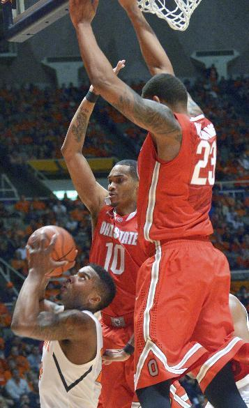 Ohio State's forward LaQuinton Ross (10) and Ohio State's center Amir Williams (23) defend a shot by Illinois' Rayvonte Rice during the first half of an NCAA college basketball game in Champaign, Ill., on Saturday, Feb. 15, 2014. (AP Photo/Robin Scholz)