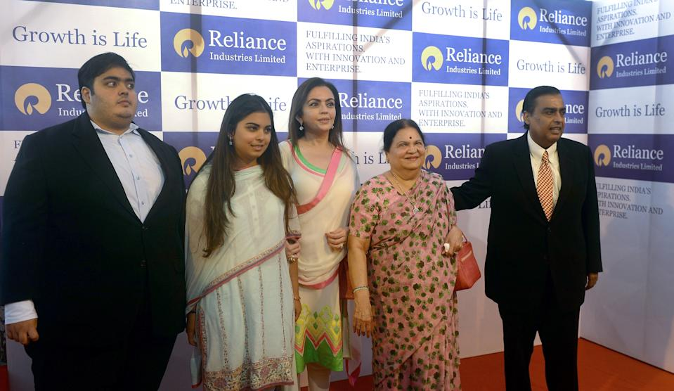 Reliance Industries Chairman Mukesh Ambani (R) poses with his mother Kokilaben (2R) his wife Nita(C) his daughter Isha (2L) and son Anant (L)on arrival at the company's annual general meeting in Mumbai on June 6, 2013. India's largest private firm Reliance Industries plans to invest 1.5 trillion rupees (USD26 billion) in all its businesses over the next three years, its chairman Mukesh Ambani told shareholders. Reliance is India's largest private oil and gas explorer with a strong presence in the petrochemicals and polyester sectors and has expanded into the fast-growing broadband and retail segments in recent years. AFP PHOTO/Indranil MUKHERJEE