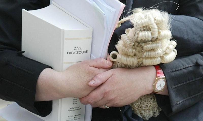 A female barrister holds her wig as she enters the Royal Courts of Justice in London