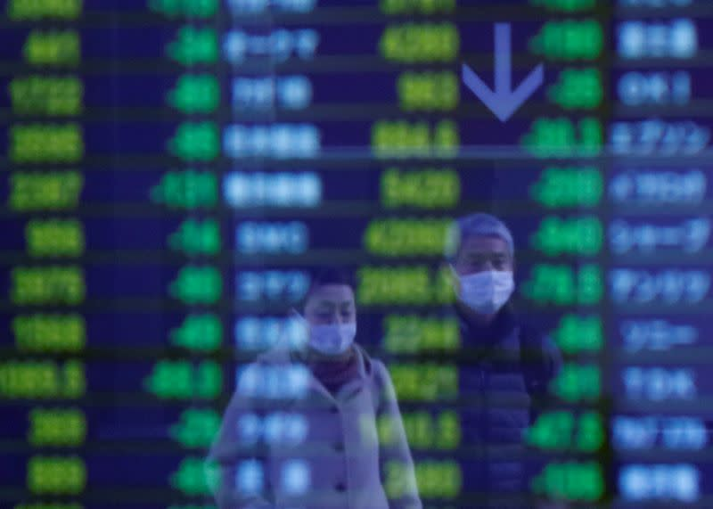 Passersby wearing protective face masks, following an outbreak of the coronavirus, are reflected on a screen displaying stock prices outside a brokerage in Tokyo