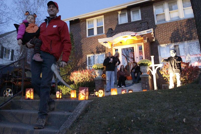Republican vice presidential candidate, Rep. Paul Ryan, R-Wis., carries his niece Zaydee May Ryan while out trick or treating with his family, Wednesday, Oct. 31, 2012, in Janesville, Wis. (AP Photo/Mary Altaffer)