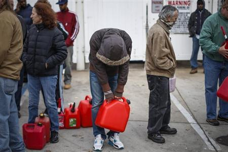 Man stands exhausted while waiting for over five hours to receive fuel from a gas station in Queens, a borough in New York