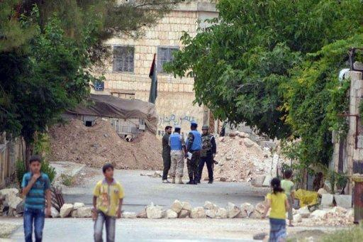 "An image released by the Syrian opposition's Shaam News Network shows Syrian children walking by as UN monitors speak to Syrian government soldiers as they visit the town of Kfra Nubul. Russia condemned as counterproductive a harsher diplomatic tone against the Syrian government on Wednesday, as the opposition accused Moscow of encouraging ""savage crimes"" in the country"