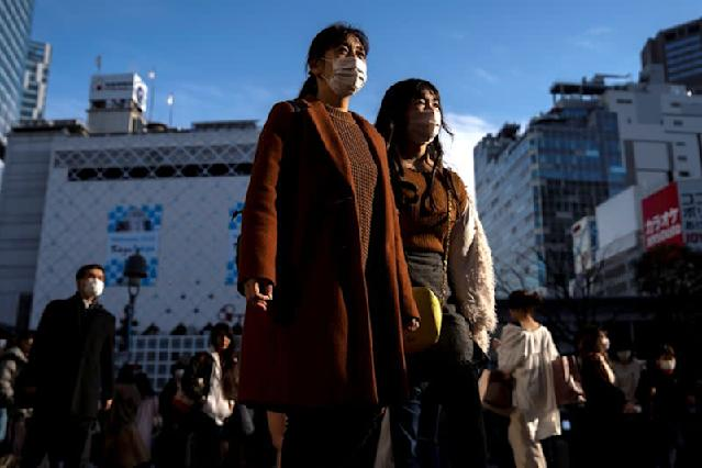 People wearing protective masks are seen at the scramble crossing in Shibuya shopping district, also known as Shibuya crossing, following an outbreak of the coronavirus in Tokyo