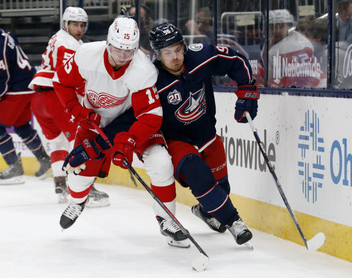 Detroit Red Wings forward Jakub Vrana, left, controls the puck in front of Columbus Blue Jackets forward Jack Roslovic during the first period of an NHL hockey game in Columbus, Ohio, Saturday, May 8, 2021. (AP Photo/Paul Vernon)