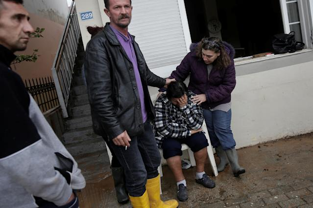 <p>Maria Kriada is comforted outside her destroyed house following flash floods which hit areas west of Athens on November 15 killing at least 15 people, in Nea Peramos, Greece, Nov. 16, 2017. (Photo: Alkis Konstantinidis/Reuters) </p>