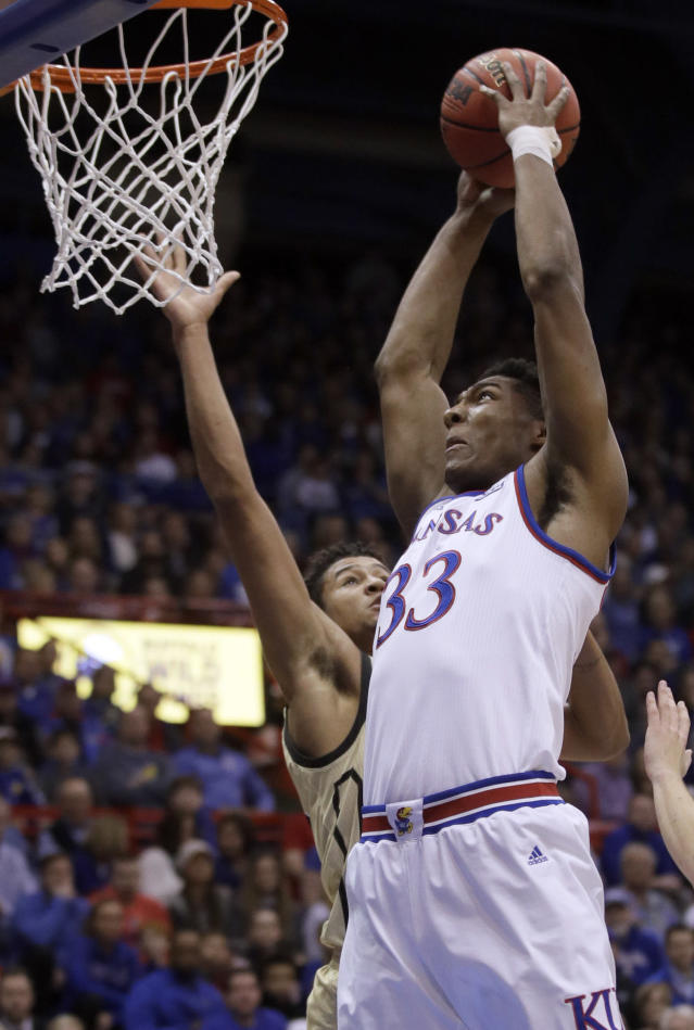 Kansas forward David McCormack (33) dunks against Wofford forward Keve Aluma, back, during the first half of an NCAA college basketball game in Lawrence, Kan., Tuesday, Dec. 4, 2018. (AP Photo/Orlin Wagner)