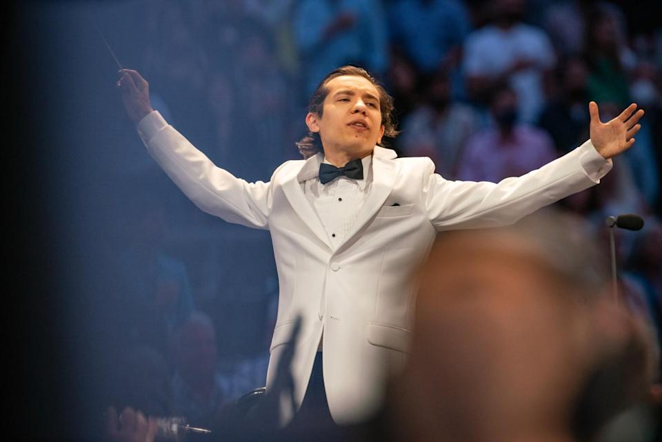 A conductor in a white suit jacket and bowtie spreads his arms wide