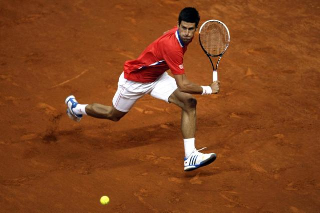 Serbia's Novak Djokovic races to return a ball to Canada's Milos Raonic during their Davis Cup semifinals tennis match in Belgrade, Serbia, Sunday, Sept. 15, 2013. (AP Photo/ Marko Drobnjakovic)