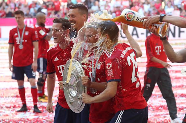 Soccer Football - Bundesliga - Bayern Munich v VfB Stuttgart - Allianz Arena, Munich, Germany - May 12, 2018 Bayern Munich's Joshua Kimmich, Sandro Wagner and Thomas Mueller celebrate winning the Bundesliga with the trophy while a beverage is thrown over them REUTERS/Michael Dalder DFL RULES TO LIMIT THE ONLINE USAGE DURING MATCH TIME TO 15 PICTURES PER GAME. IMAGE SEQUENCES TO SIMULATE VIDEO IS NOT ALLOWED AT ANY TIME. FOR FURTHER QUERIES PLEASE CONTACT DFL DIRECTLY AT + 49 69 650050