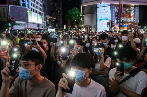 Hong Kong pro-democracy activists hold up their mobile phones during a rally iin June