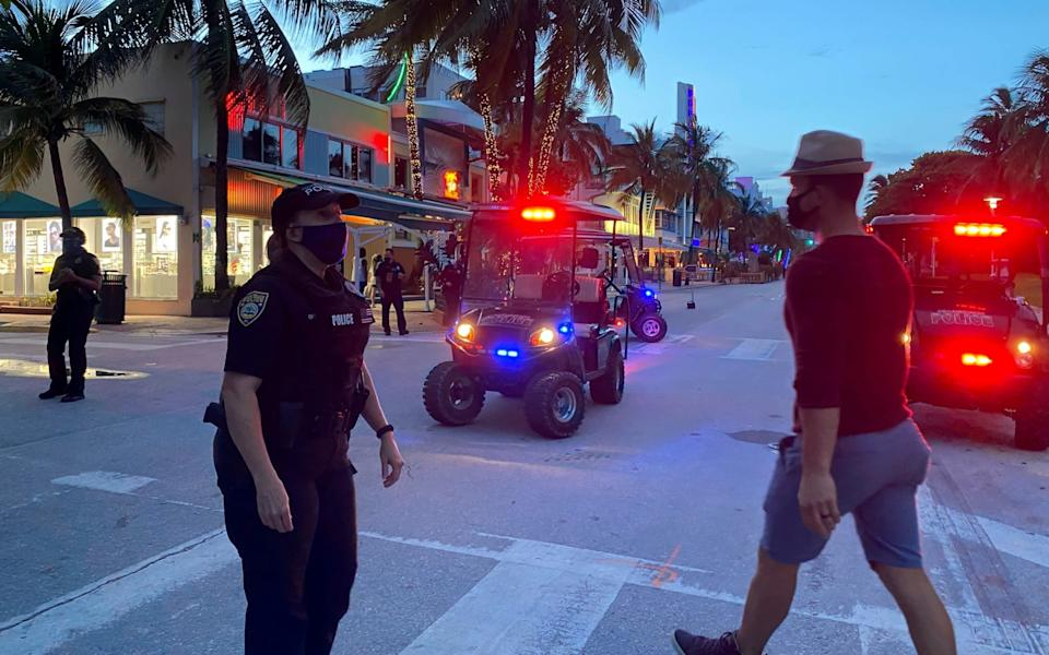 Police officers maintain the 8pm curfew imposed due to Florida's climbing numbers of cases - Reuters