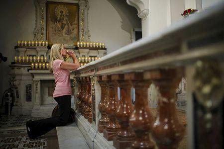 A woman prays while people attend the last mass at Church of Our Lady Peace in New York July 31, 2015. REUTERS/Eduardo Munoz