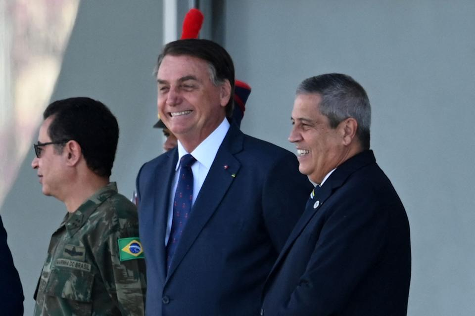 Brazilian President Jair Bolsonaro (C) smiles next to his Defense Minister Braga Netto (2R), Navy Commander Almir Garnier (L), during a military vehicles parade in front of the Planalto Palace in Brasilia, on August 10, 2021. - Bolsonaro is accused of using the armed forces for a show of force to intimidate National Congress, where a bill is being debated to modify the electronic voting system. (Photo by EVARISTO SA / AFP) (Photo by EVARISTO SA/AFP via Getty Images)