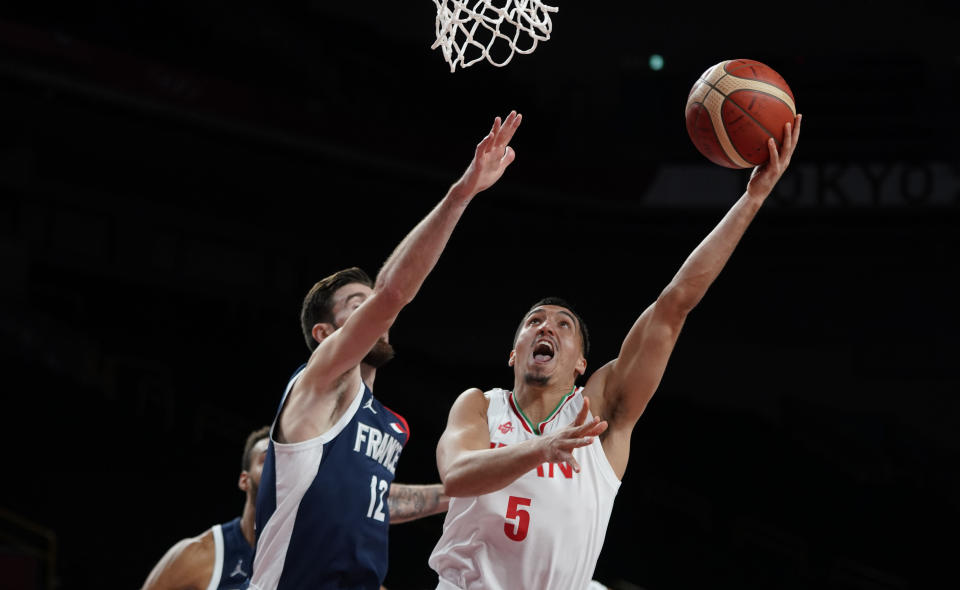 Iran's Pujan Jalalpoor (5), right, shoots ahead of France's Nando de Colo (12) during men's basketball preliminary round game at the 2020 Summer Olympics, Saturday, July 31, 2021, in Saitama, Japan. (AP Photo/Charlie Neibergall)