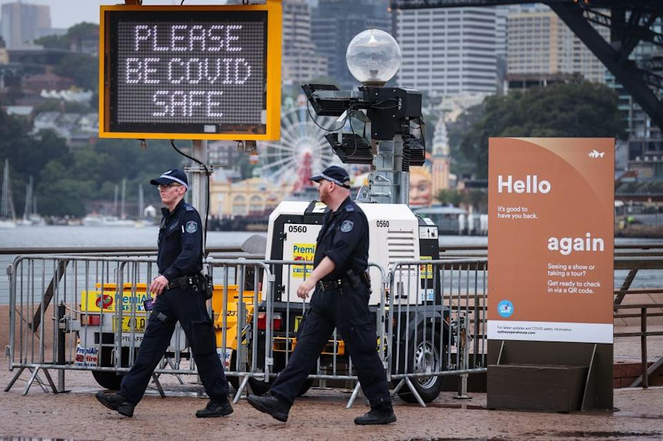 New South Wales police officers walk past signs on display in front of the Sydney Opera House.