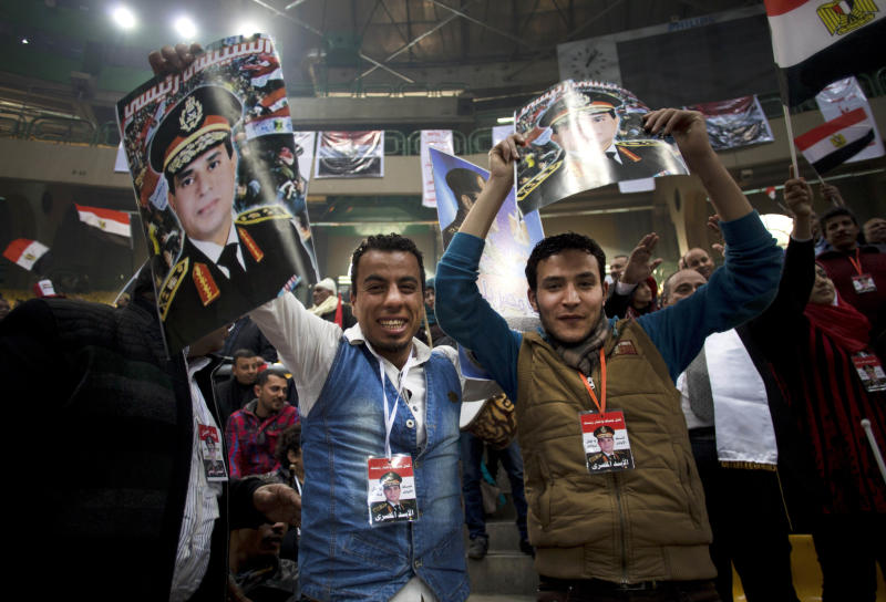 """Egyptians hold posters of Egypt's Defense Minister, Gen. Abdel-Fattah el-Sissi, with Arabic writing that reads, """"el-Sissi is my president,"""" during a rally in support of el-Sissi, in Cairo, Egypt, Tuesday, Jan. 21, 2014. Supporters of the powerful army chief and defense minister urged Egyptians on Tuesday to turn the third anniversary to 2011 uprising that toppled longtime autocratic president Hosni Mubarak, to a show of gratitude to the general for ousting Islamist president, calling on him to contest elections. (AP Photo/Khalil Hamra)"""