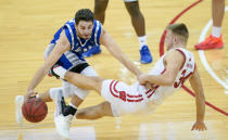 Wisconsin's Brad Davison (34) fouls Eastern Illinois' Josiah Wallace (22) during the first half of an NCAA college basketball game Wednesday, Nov. 25, 2020, in Madison, Wis. (AP Photo/Andy Manis)