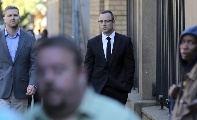 Oscar Pistorius, center, with an unidentified family member walks towards the high court in Pretoria, South Africa, Tuesday, May 13, 2014. Pistorius is charged with murder for the shooting death of his girlfriend, Reeva Steenkamp, on Valentines Day in 2013. (AP Photo/Themba Hadebe)