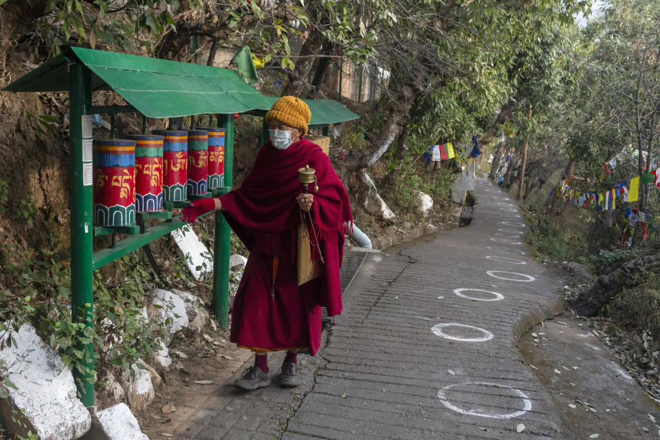 An exile Tibetan Buddhist monk rotates prayer wheels next to a path marked with circles for voters to ensure social distancing in Dharmsala, India, Sunday, Jan. 3, 2021. Exile Tibetans Sunday voted in the first round to elect a new political leader and members of the Tibetan parliament in exile. (AP Photo/Ashwini Bhatia)