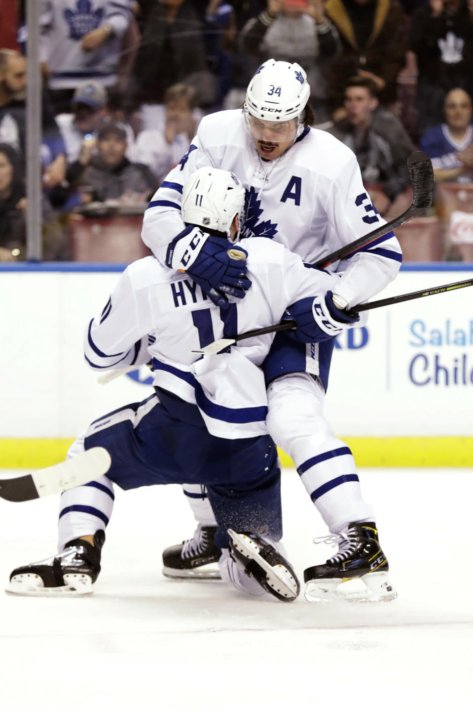 Toronto Maple Leafs left wing Zach Hyman (11) congratulates center Auston Matthews (34) after Matthews scored during the first period of the team's NHL hockey game against the Florida Panthers, Thursday, Feb. 27, 2020, in Sunrise, Fla. (AP Photo/Wilfredo Lee)