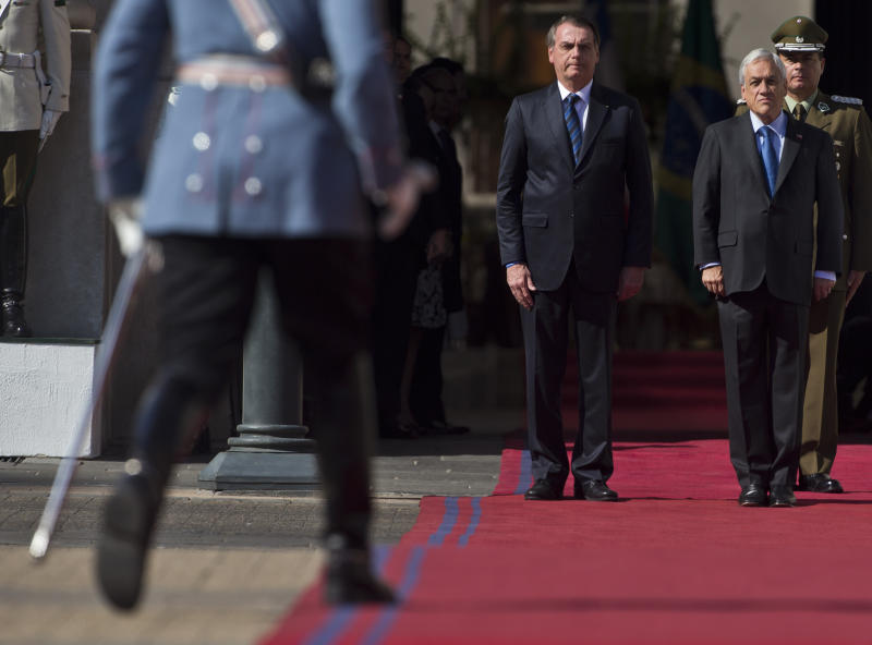 Brazil's President Jair Bolsonaro, left, and Chilean President Sebastian Pinera, receive military honors in front of the presidential palace La Moneda,in Santiago, Chile, Saturday, March 23, 2019. Bolsonaro is on the second day of his two-day visit. (AP Photo/Esteban Felix)