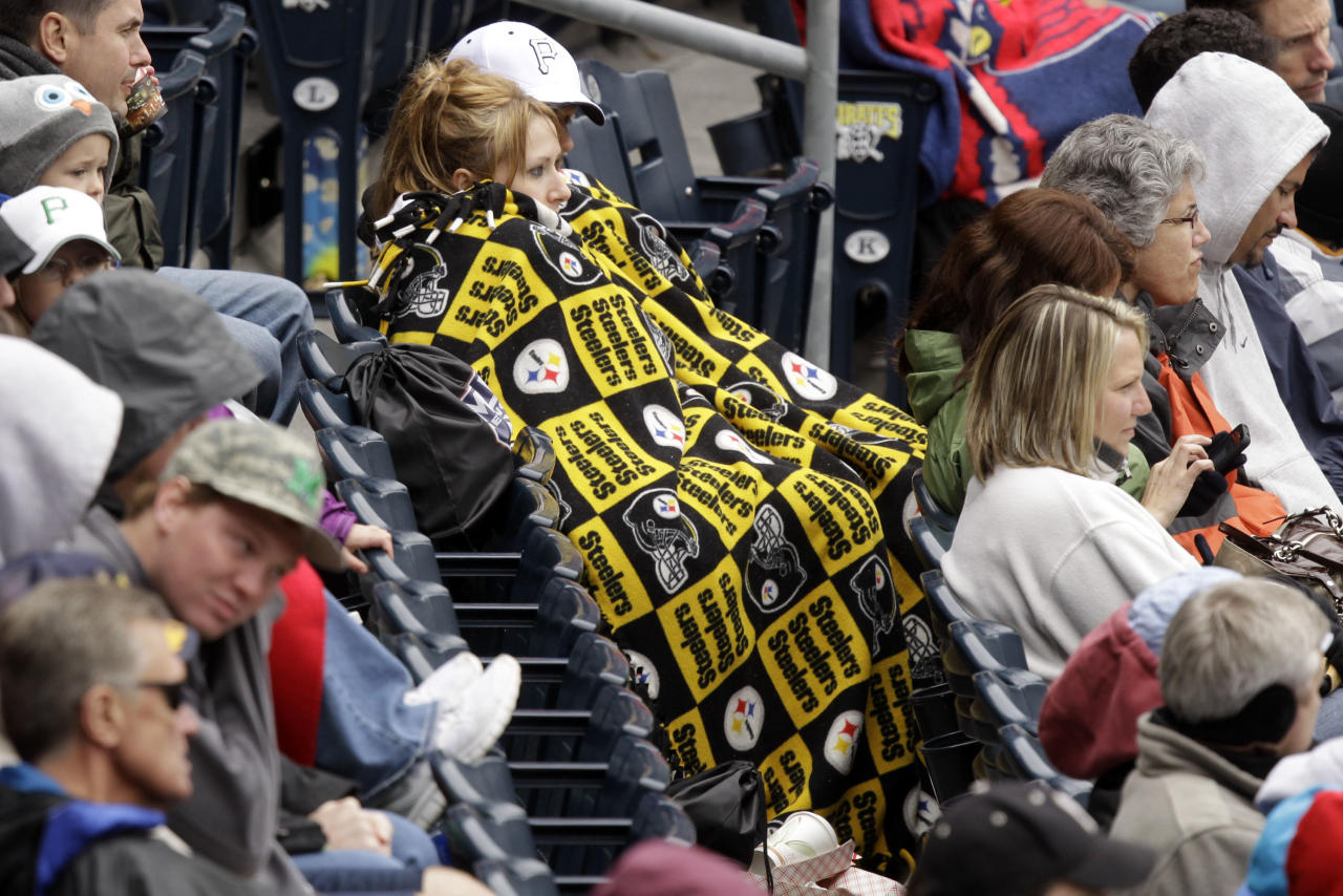 Pittsburgh Pirates fans sit bundled in a Pittsburgh Steelers blanket while watching a baseball game between the St. Louis Cardinals and the Pirates in Pittsburgh on Sunday, April 22, 2012. The Cardinals won 5-1. A spring nor'easter rumbled along the East Coast on Sunday and was expected to bring rain and heavy winds and even snow in some places as it strengthens into early Monday, a punctuation to a relatively dry stretch of weather for the Northeast. (AP Photo/Gene J. Puskar)