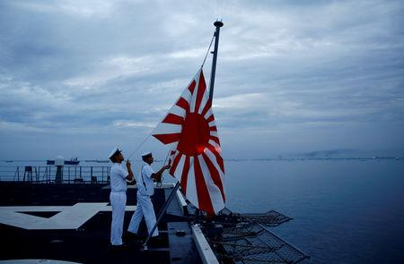Sailors lower the Japanese naval ensign at a flag lowering ceremony on the deck of Japanese helicopter carrier Kaga anchored near Jakarta Port ahead of its departure for naval drills in the Indian Ocean, Indonesia September 21, 2018. Picture taken on September 21, 2018.  REUTERS/Kim Kyung-Hoon
