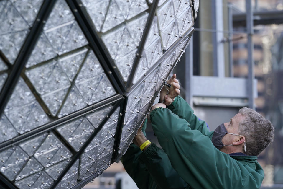 Workers from Landmark Signs install a panel of Waterford crystal triangles on the Times Square New Year's Eve ball, Sunday, Dec. 27, 2020, in New York, in preparation for the New Year's Eve ball drop. (AP Photo/Kathy Willens)