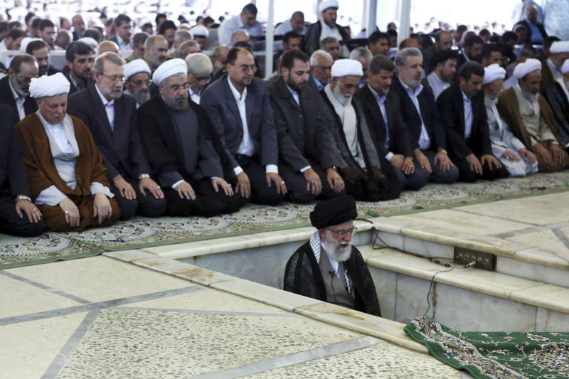 In this picture released by an official website of the office of the Iranian Supreme Leader Ayatollah Ali Khamenei, Khamenei, foreground, leads his sermon of Eid al-Fitr prayer, marking the start in Iran of the Eid al-Fitr holiday at the end of the holy month of Ramadan at the Tehran University campus in Tehran, Iran, Friday, Aug. 9, 2013. Khamenei lashed out at the Unites States, saying America is not a good mediator in Mideast peace talks because it allegedly sides with Israel. (AP Photo/Office of the Iranian Supreme Leader)