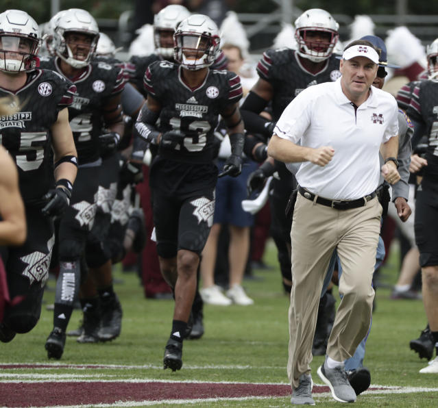 Mississippi State head coach Dan Mullen leads his team onto the field for their NCAA college football game against Massachusetts in Starkville, Miss., Saturday, Nov. 4, 2017. No. 21 Mississippi State won 34-23. (AP Photo/Rogelio V. Solis)
