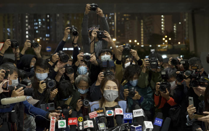 Clarisse Yeung, center, one of the 47 pro-democracy activists charged with conspiracy, gestures outside a court after being released in Hong Kong, Friday, March 5, 2021. Four of the 47 pro-democracy activists charged with conspiracy to commit subversion were released on bail Friday, after prosecutors dropped an appeal against the court's decision to grant them bail. (AP Photo/Vincent Yu)